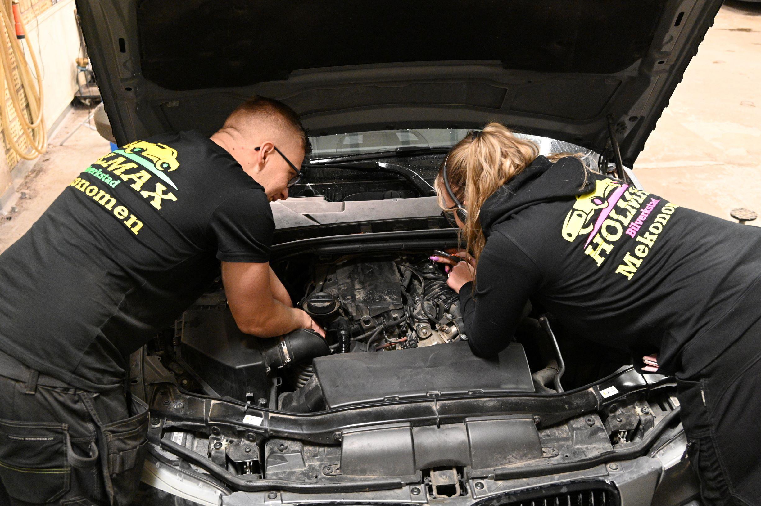 Två personer som lagar en bil